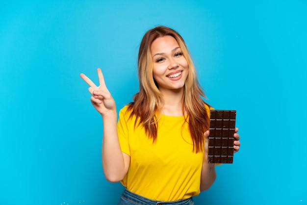 Teenager girl holding chocolat over isolated blue background smiling and showing victory sign
