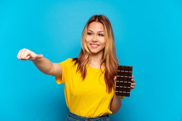 親指を立てるジェスチャーを与える孤立した青い背景の上にショコラを保持しているティーンエイジャーの女の子