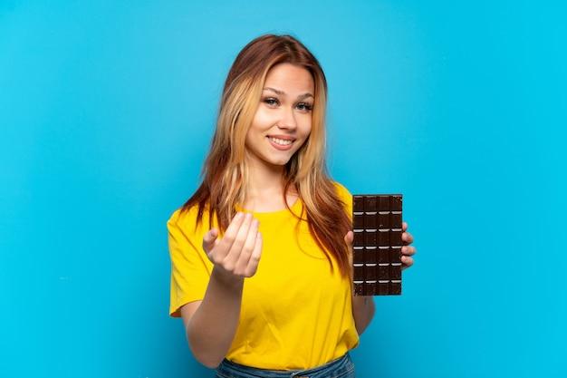 手で来るように誘う孤立した青い背景の上にチョコレートを保持しているティーンエイジャーの女の子。あなたが来て幸せ