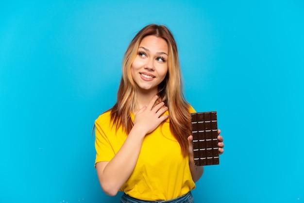 笑顔で見上げる孤立した青い背景の上にショコラを保持しているティーンエイジャーの女の子