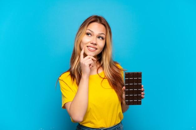Девушка-подросток держит шоколад на изолированном синем фоне, думая об идее, глядя вверх