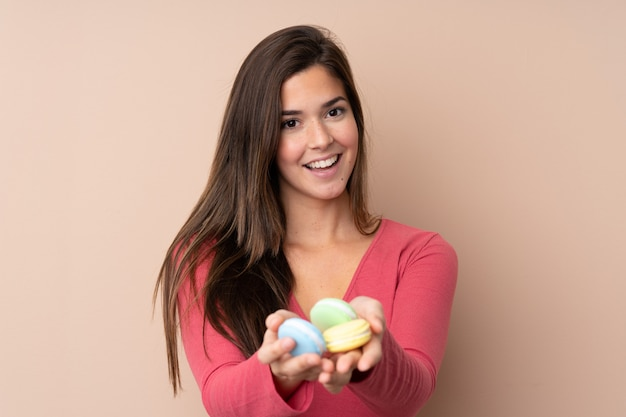 Teenager girl holding colorful french macarons