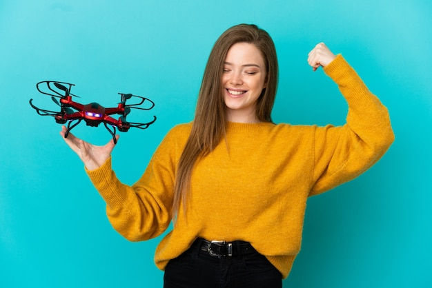 Teenager girl holding a drone over isolated blue background doing strong gesture