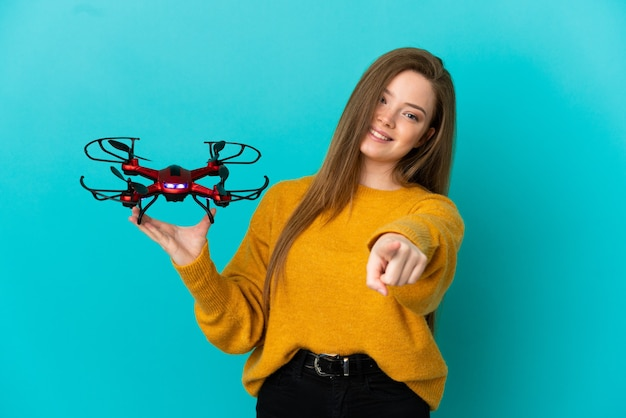 Teenager girl holding a drone over isolated blue background pointing front with happy expression