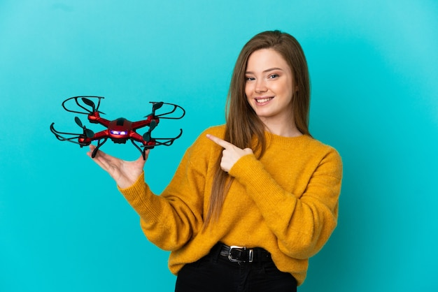 Teenager girl holding a drone over isolated blue background pointing to the side to present a product