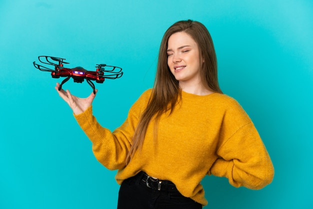Teenager girl holding a drone over isolated blue background suffering from backache for having made an effort