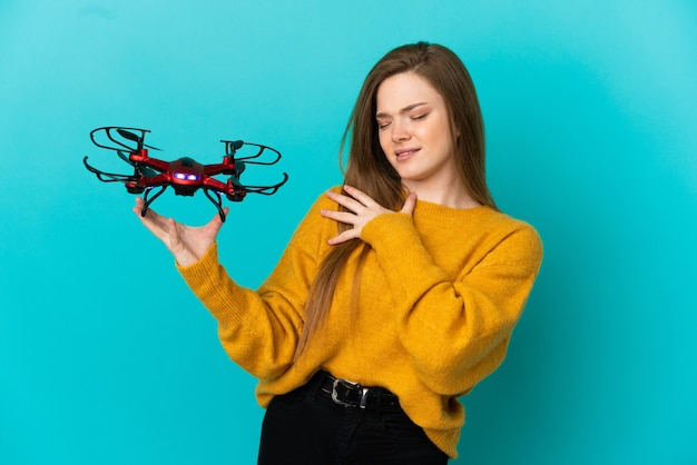 Teenager girl holding a drone over isolated blue background suffering from pain in shoulder for having made an effort