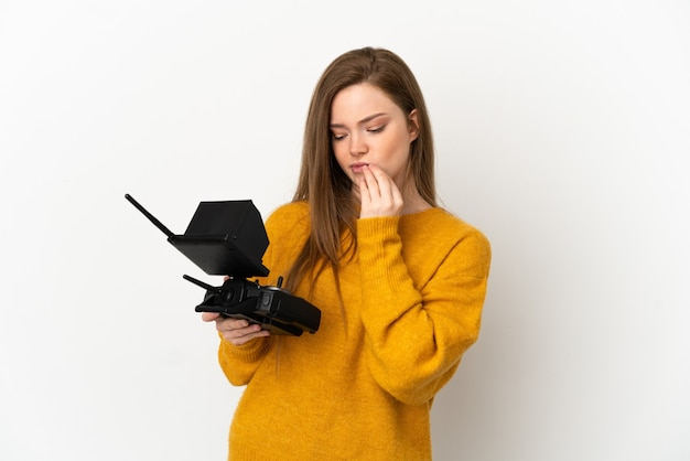 Teenager girl holding a drone remote control over isolated white background having doubts