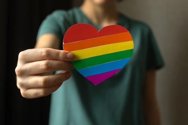 Lgbt 무지개 색상으로 마음을 잡고 십 대 소녀입니다. 프라이드 월, 게이 및 레즈비언 관용 conceot 배경 사진