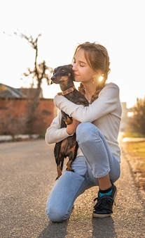 Teenager girl holding her dachshund dog in her arms outdoors in sunset
