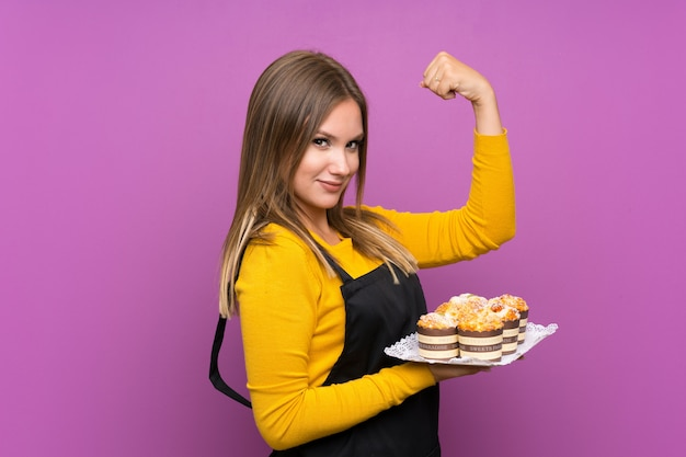 Teenager girl holding lots of different mini cakes over isolated purple making strong gesture