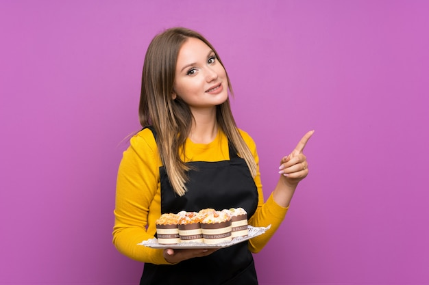 Teenager girl holding lots of different mini cakes over isolated purple wall pointing finger to the side