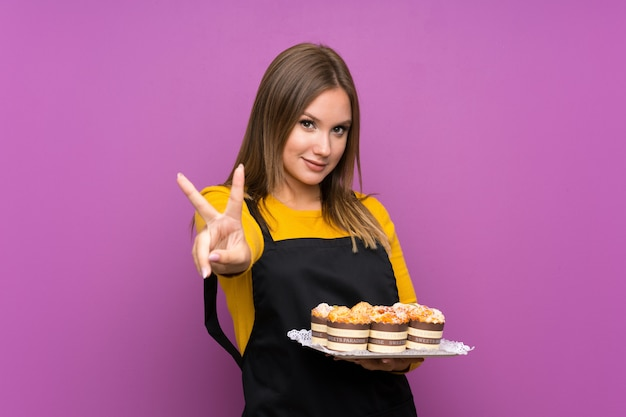 Teenager girl holding lots of different mini cakes over isolated purple wall smiling and showing victory sign