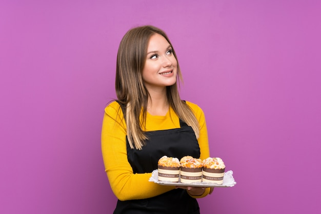 Teenager girl holding lots of different mini cakes purple laughing