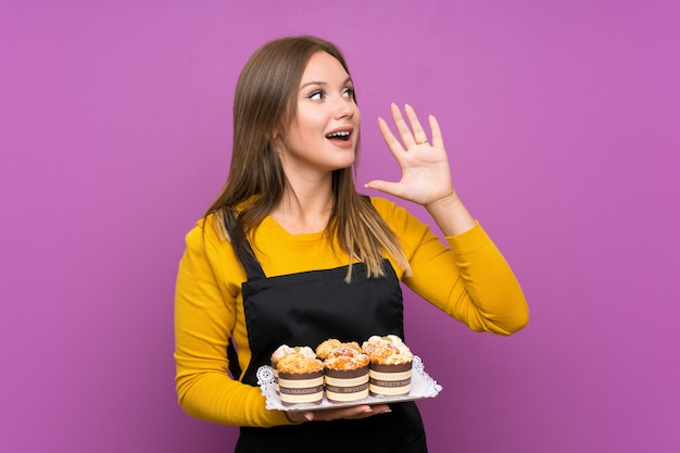 Teenager girl holding lots of different mini cakes purple shouting