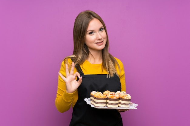 Teenager girl holding lots of different mini cakes purple showing an ok sign with fingers