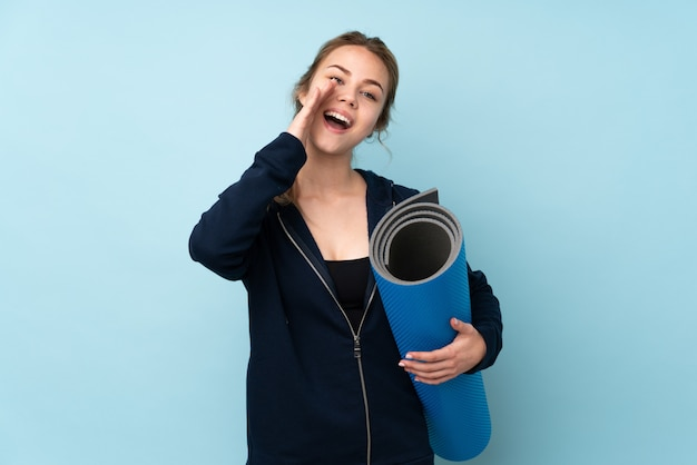 Teenager girl holding mat on blue shouting and announcing something