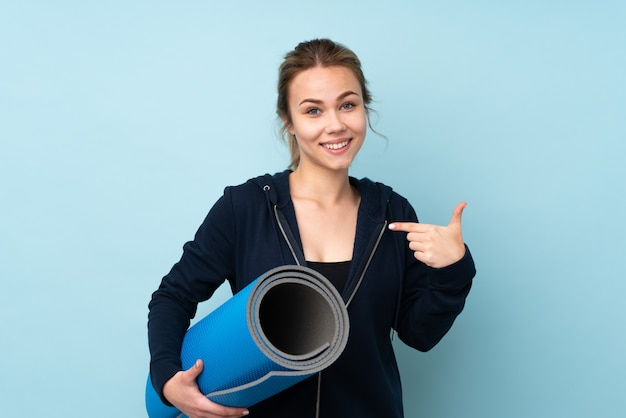 Teenager girl holding mat on blue wall with surprise facial expression
