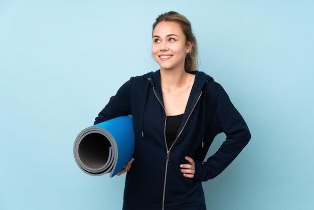 Девушка-подросток держит циновку, изолированную на синем, позирует с руками на бедрах и улыбается
