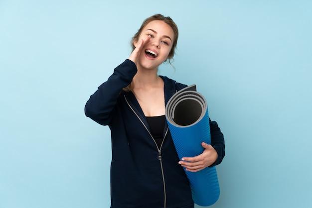 Девушка подростка держа циновку на сини крича и объявляя что-то