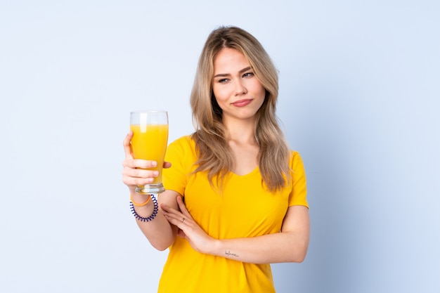 Teenager girl holding an orange juice on blue wall with sad expression