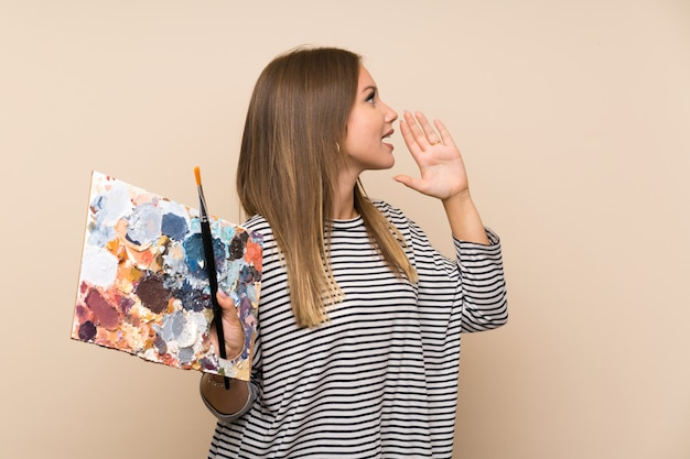 Teenager girl holding a palette shouting with mouth wide open