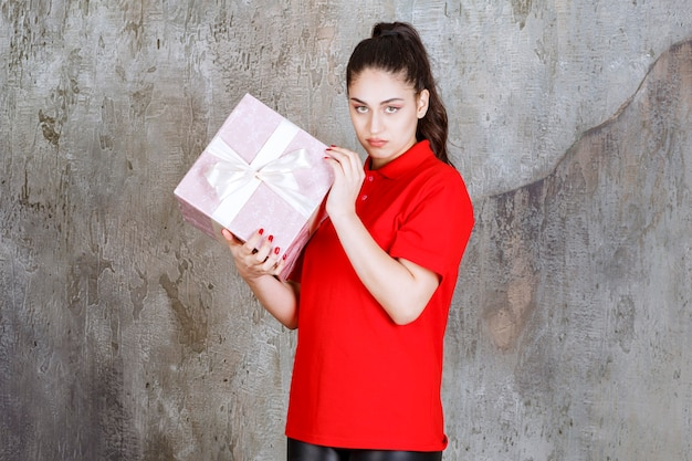 Teenager girl holding a pink gift box wrapped with white ribbon and looks dissatisfied