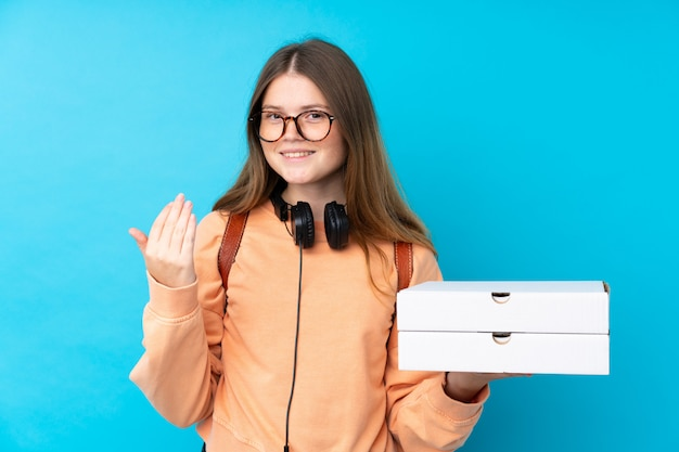 Teenager girl holding pizzas over isolated blue wall inviting to come with hand.