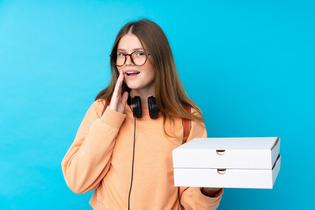 Teenager girl holding pizzas over isolated blue wall shouting with mouth wide open