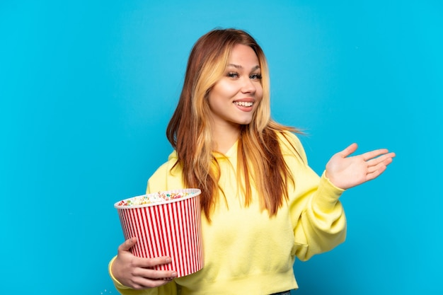 Teenager girl holding popcorns over isolated blue background extending hands to the side for inviting to come