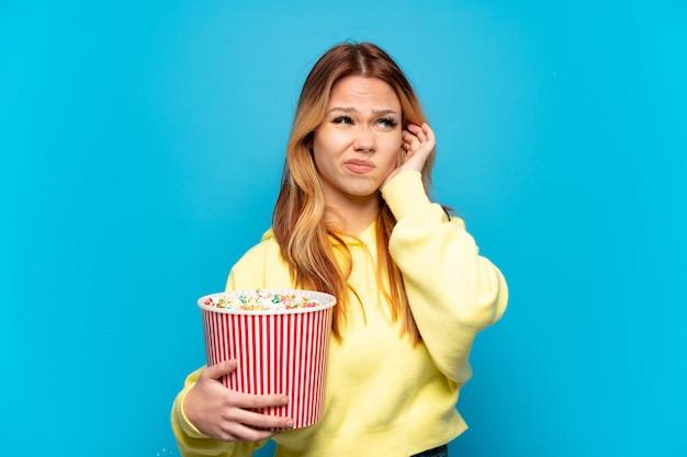 Девушка-подросток держит попкорн на изолированном синем фоне разочарована и закрывает уши