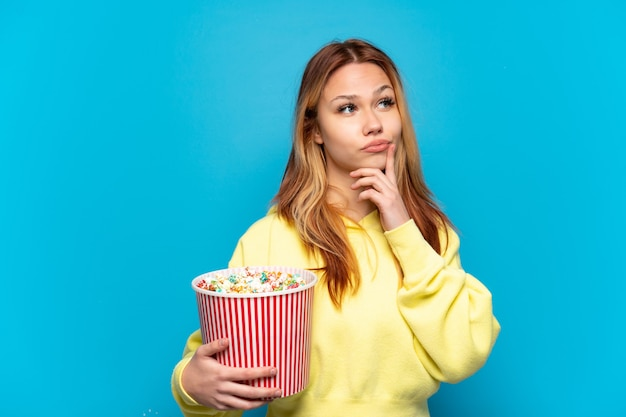 Teenager girl holding popcorns over isolated blue background having doubts while looking up