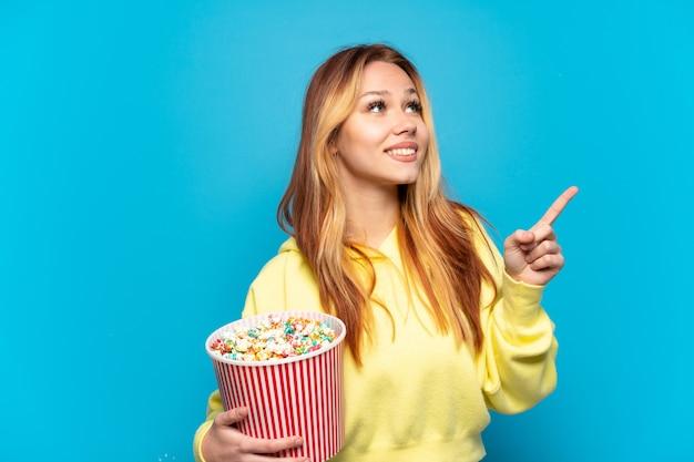 Девушка-подросток держит попкорн на изолированном синем фоне, указывая на отличную идею