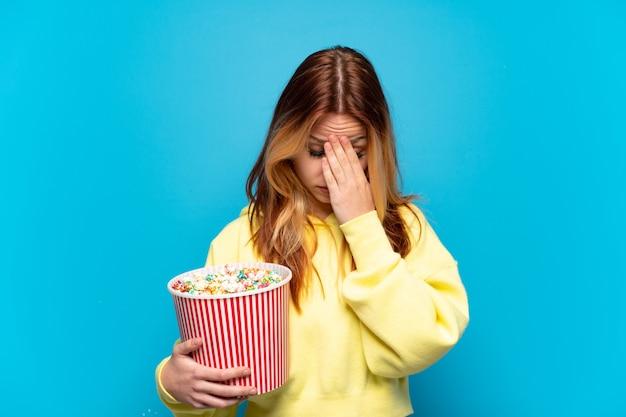 疲れて病気の表情で孤立したポップコーンを持った 10 代の少女
