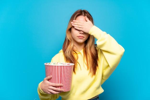 手で目を覆っている孤立した青い背景の上にポップコーンを保持しているティーンエイジャーの女の子。何かを見たくない