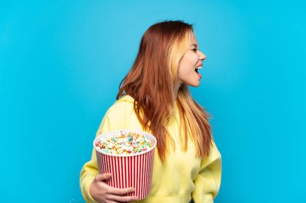 Девушка-подросток держит попкорн на изолированном синем фоне, смеясь в боковом положении