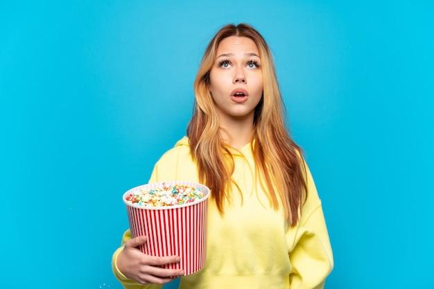 Девушка-подросток держит попкорн на изолированном синем фоне, глядя вверх и с удивленным выражением лица