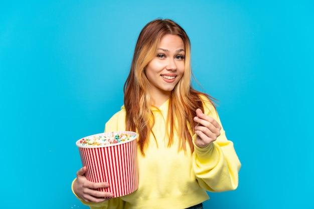 Девушка-подросток держит попкорн на изолированном синем фоне, делая денежный жест