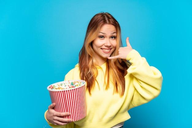 Девушка-подросток, держащая попкорн на изолированном синем фоне, делая телефонный жест. перезвони мне знак
