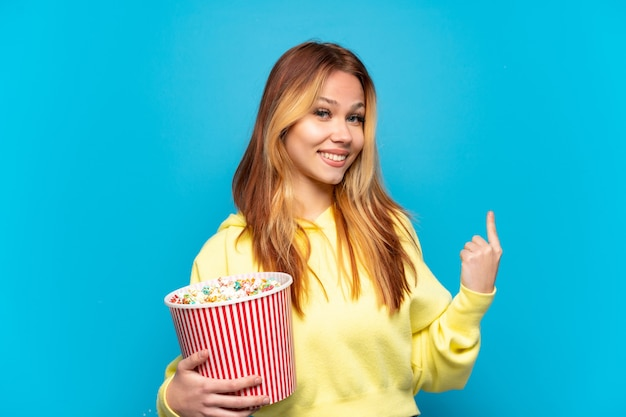 Девушка-подросток держит попкорн на изолированном синем фоне, указывая назад