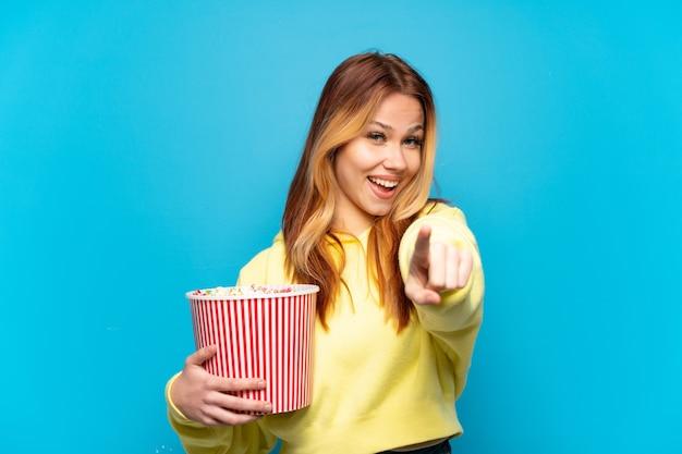 Девушка-подросток держит попкорн на изолированном синем фоне, указывая вперед с счастливым выражением лица