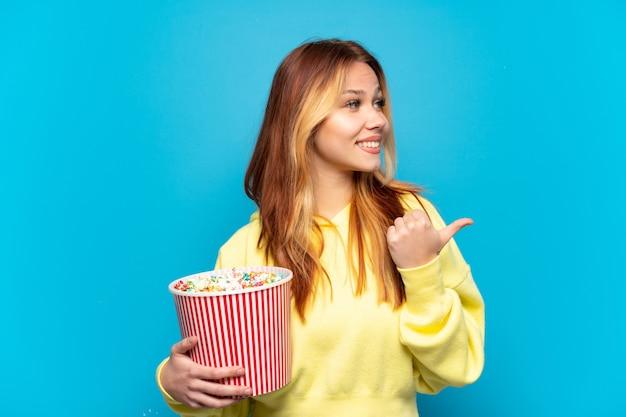 Девушка-подросток держит попкорн на изолированном синем фоне, указывая в сторону, чтобы представить продукт