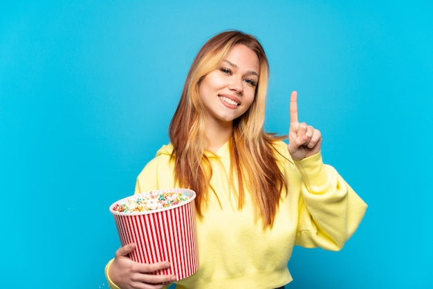 Девушка-подросток держит попкорн на изолированном синем фоне, показывая и поднимая палец в знак лучшего