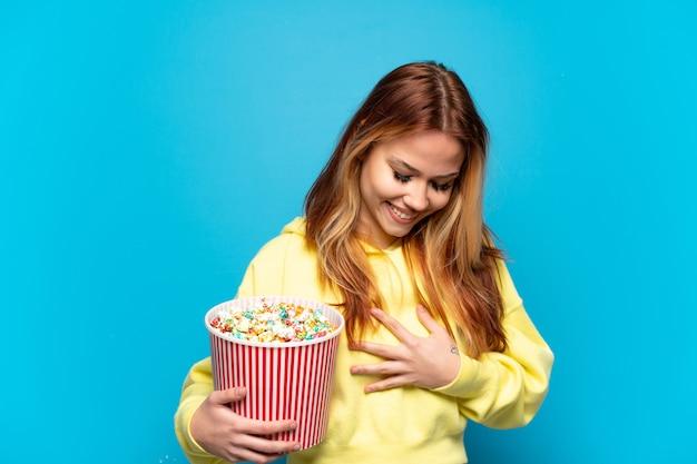 たくさん笑って孤立した青い背景の上にポップコーンを保持しているティーンエイジャーの女の子