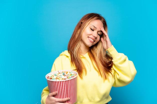 Девушка-подросток держит попкорн на синем фоне, много улыбаясь
