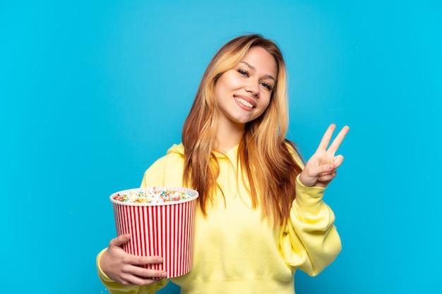 笑顔と勝利のサインを示す孤立した青い背景の上にポップコーンを保持しているティーンエイジャーの女の子