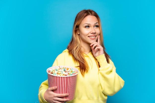 Девушка-подросток держит попкорн на изолированном синем фоне, думая об идее, глядя вверх