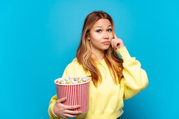 Девушка-подросток держит попкорн на изолированном синем фоне, думая об идее