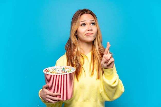Девушка-подросток держит попкорн на синем фоне со скрещенными пальцами и желает всего наилучшего