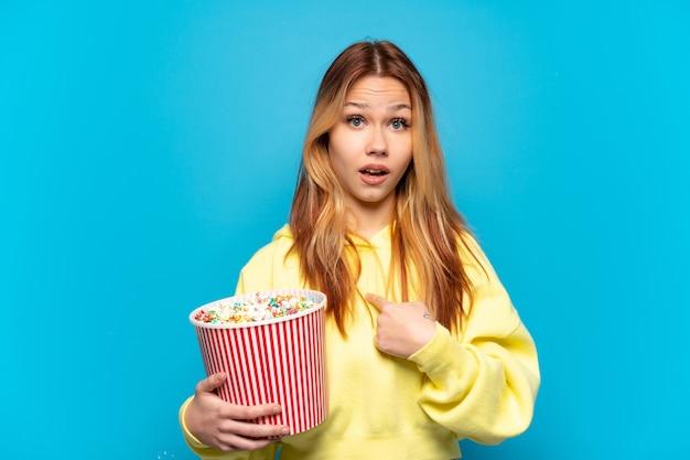 Девушка-подросток держит попкорн на синем фоне с удивленным выражением лица